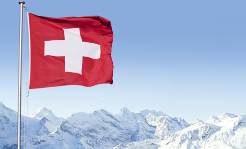 Swiss flag flying over the mountains